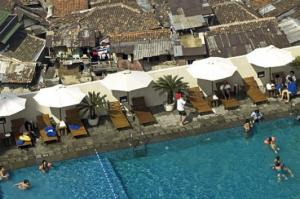 Het terrein van een luxe hotel wordt slechts door een muur gescheiden van de kampong. (Foto: Y. Effendy)